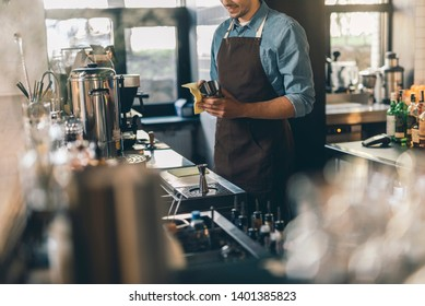 Close up of a smiling young bartender standing at his workplace with a cocktail shaker and cleaning it carefully