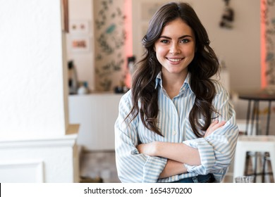 Close up of a smiling young brunette woman wearing formal shirt standing in the cafe indoors, arms folded - Shutterstock ID 1654370200