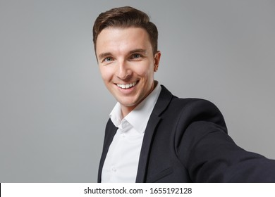 Close up of smiling young business man in classic black suit shirt isolated on grey wall background. Achievement career wealth business concept. Mock up copy space. Doing selfie shot on mobile phone