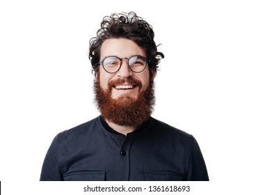Close up smiling young businessman wearing eyeglasses, looking at the camera against white wall background