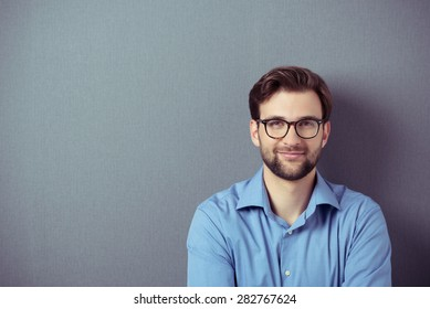 Close up Smiling Young Businessman Wearing Eyeglasses, Looking at the Camera Against Gray Wall Background with Copy Space