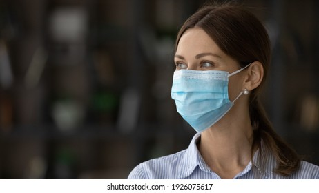 Close up of smiling young Caucasian woman in facial mask look in distance think dream of coronavirus pandemics end. Happy female in facemask against corona virus epidemics. Covid-19 concept.