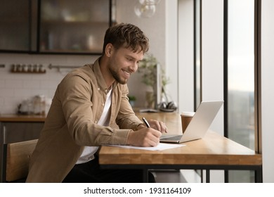 Close up smiling young man using laptop, writing, taking notes, watching webinar, training, involved in internet lesson, motivated positive student studying online at home, looking at laptop screen