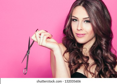 close up of a smiling young woman with beautiful hair, hold scissors in one hand pink background