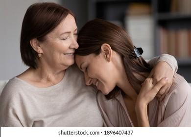Gros plan sur une jeune femme souriante et une mère mature embrassant, une mère âgée et sa fille adulte profitant d'un moment tendre, câlinant, se tenant la main, une famille heureuse passant du temps libre à la maison