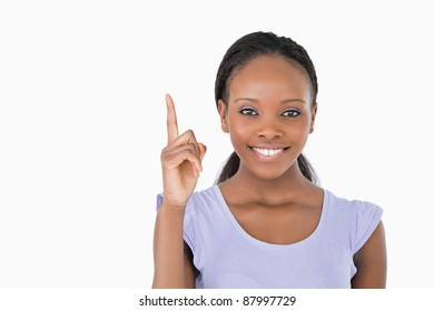 Close up of smiling young woman pointing upwards on white background