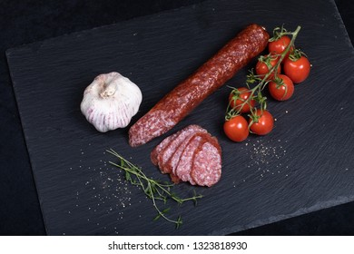 Close up of smocked sausage with garlic and cherry tomatoes