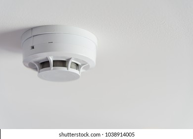 Close up smoke detector on a ceiling.