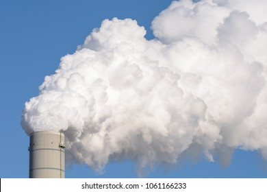 Close up of a smokestack of a fossil fuel coal power plant with white smoke against a completely blue sky and lots of copy space.