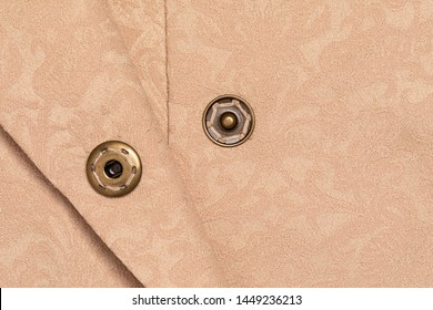 Close up snap button on coffee color fabric clothes with copy space. Extreme close up sewing background clothing detail with negative space. Poppers button sewing on textile with rough texture.