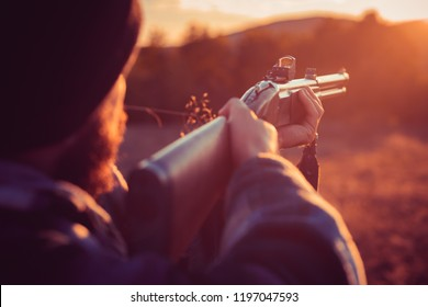 Close up snipers carbine at the outdoor hunting. Rifle Hunter Silhouetted in Beautiful Sunset. Autumn hunting season. Track down