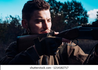Close up snipers carbine at the outdoor hunting. Close up Portrait of hamdsome Hunter. Hunter with shotgun gun on hunt