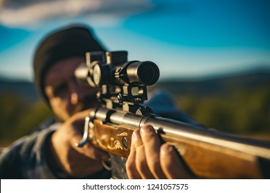 Close up snipers carbine at the outdoor hunting. Hunter aiming rifle in forest. Hunter with shotgun gun on hunt. Hunter with Powerful Rifle with Scope Spotting Animals