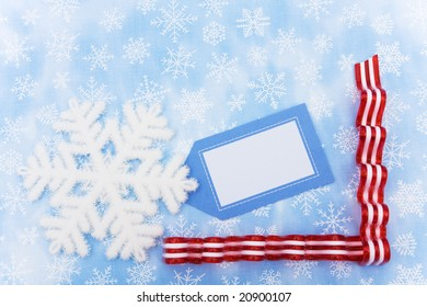 Close up of snowflake with a blank gift tag and red ribbon candy on a snowflake background, snowflake background