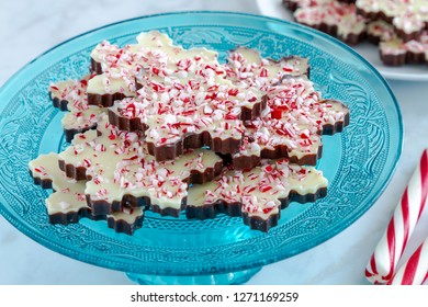 Close up of snowflake shaped chocolate peppermint bark on blue glass platter with additional plate in background