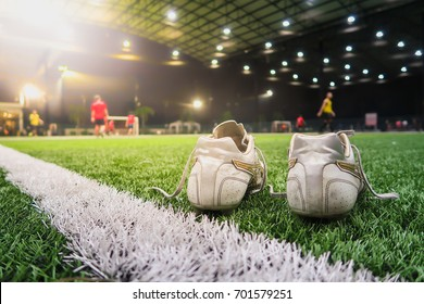 Close up the soccer boots on artificial grass of indoor soccer or football field