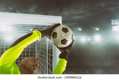 Close up of a soccer goalkeeper saving the ball at the corner of the goalposts