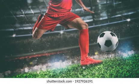 Close up of a soccer scene at night match with player in a red uniform kicking the ball with power - Shutterstock ID 1927926191