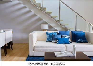 Close up of sofa in living room decorated with blue pillows. Duplex interior decorated by contemporary styles. White sofa in living room and decorated with blue indigo pillows.