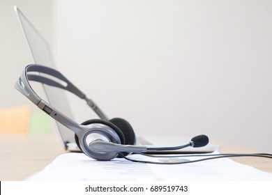close up soft focus blurred of headset of call centre at computer office room with financial report concept.