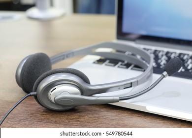 close up soft focus headphone call centre hotline at computer office desk concept