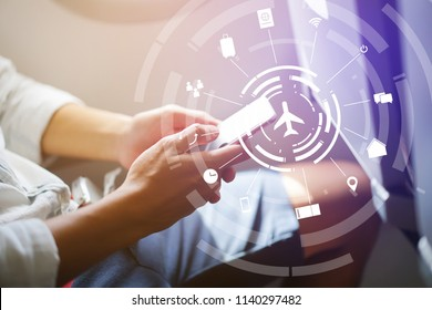 close up soft focus on businessman hand holding smartphone for checking work or playing in the aircraft with virtual interface of air transportation symbol technology,business travel concept