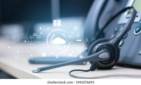 close up soft focus on headset with telephone devices at office desk for customer service support with Saas technology communication icon concept