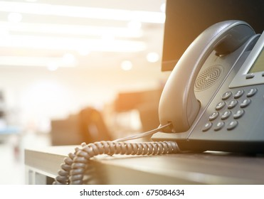 close up soft focus on telephone devices at office desk with light effect,communication technology concept