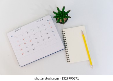close up soft focus on top view calendar april 2019 with notebook,pen and plant at office desk with top view concept
