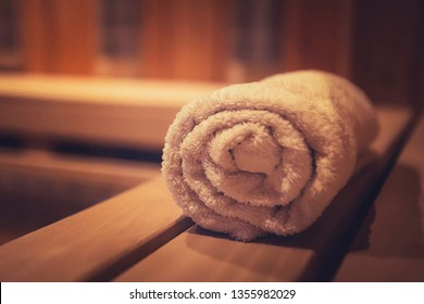 A close up of a soft terry bath towel in a wooden steam sauna. Comfortable rest in a traditional Russian cedar bath. Execellent conviniences for relaxation in steam room of eco-designed sauna