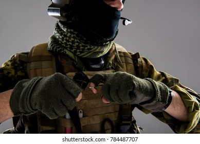 Close up soldier hands pulling out joint pin from grenade. War concept