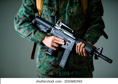 Close up of soldier holding a rifle with both hands and wearing a military uniform, in a gray background