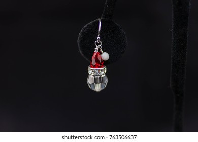 close up of a solitary beaded red, silver and white Santa Claus earring