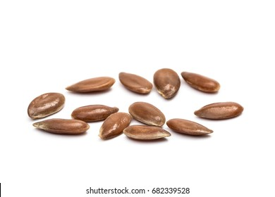 Close up of some linseeds on white background seen obliquely from above with focus on the closest