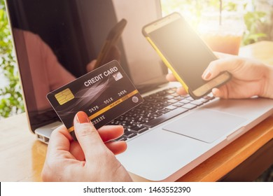 Close up of someone hand holding credit card during using laptop and mobile phone for online shopping. Online shopping is the process of buying goods and services from merchants over the Internet.