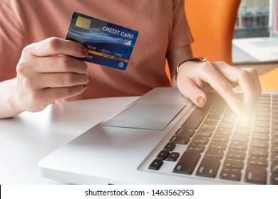 Close up of someone hand holding credit card during using laptop for online shopping. Online shopping is the process of buying goods and services from merchants over the Internet.