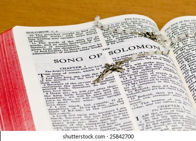 Close up of Song of Solomon bible page with rosary