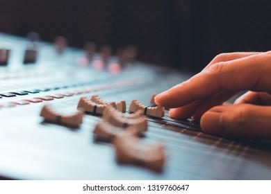 close up sound engineer, producer, dj hands adjusting sound mixer fader