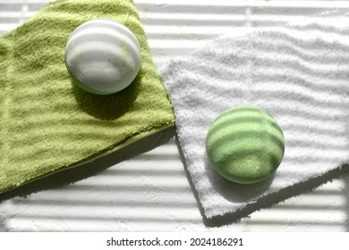 Close up spa aromatherapy composition with green bath bombs on towels. Zen concept for natural beauty cosmetic, massage. Wellness. Sunlit minimalist still life for eco products