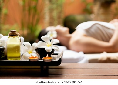Close up Spa items.  Background asian woman lying down on massage bed with scrub sugar and salt aroma at outdoor natural.  wellness center, so relax and lifestyle. Thai Day Spa.  Healthy Concept
