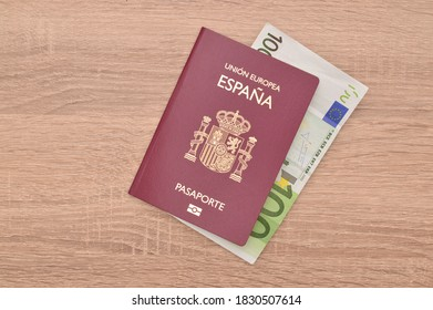 Close up Spain Passport with One Hundred Euro Paper Currency on wood grain table
