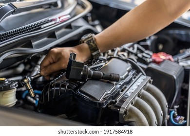 Close up spark plug coil on engine cover and a man use block wrench remove a bolt for take off coil engine service in garage and engine room  background