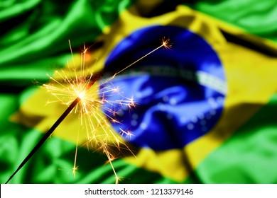 Close up of sparkler burning over Brazil, Brazilian flag. Holidays, celebration, party concept