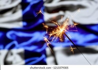 Close up of sparkler burning over Finland, Finnish flag. Holidays, celebration, party concept