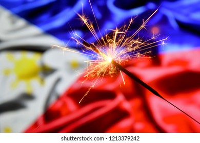 Close up of sparkler burning over Philipines flag. Holidays, celebration, party concept