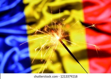 Close up of sparkler burning over Romania, Romanian flag. Holidays, celebration, party concept