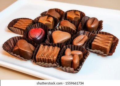 close up special chocolates with different figures in white plate on white background.