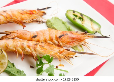 Close up of spicy whole grilled large shrimps -scampi- with guacamole sauce and grilled jalapeno pepper.