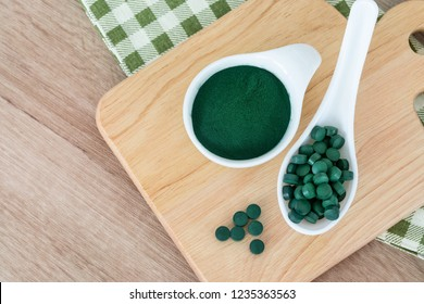 Close up  spirulina powder in bowl and spirulina pills in spoon , healthy superfood diet and detox nutrition concept
