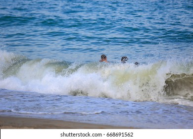 Close up of splashes of a curly turquoise wave crashing at tropical beach